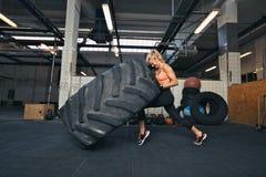 Crossfit kvinna som bläddrar ett enormt gummihjul på idrottshallen Royaltyfri Bild