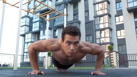 Crossfit man and lifestyle concept. doing push ups on outdoors. background buildings. Fitness, sport, exercising, training and lifestyle concept - young man stock video footage