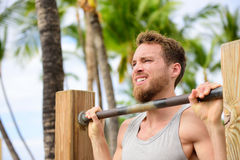 Crossfit man working out pull-ups on chin-up bar. Portrait of bearded fit young man cross training arms on horizontal bars outside on outdoor gym in summer Stock Images