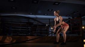 Crossfit Mujer muscular que ejercita con la cuerda en gimnasio del crossfit almacen de video