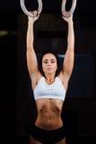 Crossfit Portrait de fille musculaire d'ajustement de jeunes dans le dessus blanc utilisant les anneaux gymnastiques images libres de droits