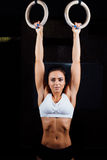 Crossfit. Portrait of young fit muscular girl in white top using gymnastic royalty free stock image