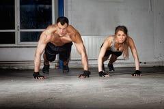 Crossfit skjuter upp övning i en idrottshall Royaltyfri Fotografi