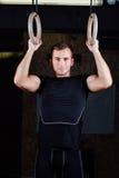 Crossfit Stående av den färdiga muskulösa mannen för barn som använder gymnastiska cirklar Royaltyfria Bilder
