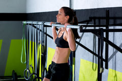 Crossfit toes to bar woman pull-ups 2 bars workout. Exercise at gym Stock Photos