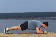 Crossfit training fitness man doing plank core exercise working out his midsection core muscles. royalty free stock photo