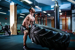 Crossfit training - man flipping tire. Shirtless man flipping heavy tire at crossfit gym royalty free stock image