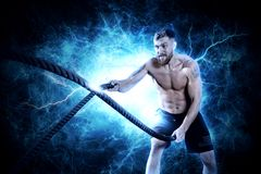 Crossfit training. Ropes. Crossfit training. Man working out with battle ropes at gym stock photo