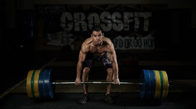 Crossfit training. Weightlifting. Sport. Endurance. Muscular shirtless athlete lifting heavy barbell in the gym Stock Image