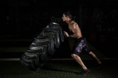Crossfit training. Young sportsman with muscular body lifting heavy wheel in gym Stock Image