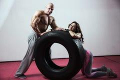 CrossFit utbildning Kvinna och man med gummihjulet Arkivfoton