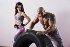 CrossFit utbildning Kvinna och man med gummihjulet Arkivbilder