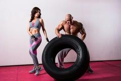 CrossFit utbildning Kvinna och man med gummihjulet Arkivbild