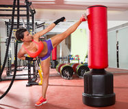 Crossfit woman kick boxing with red punching bag Stock Photo