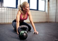 Crossfit Woman Resting. Portrait of a beautiful woman resting during her crossfit exercise with a kettlebell Stock Photography