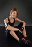 Crossfit woman sitting, isolated on black background Stock Images