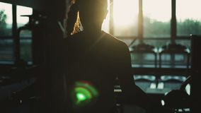 Crossfit. Woman working out in gym warming up her upper body and hands. Silhouette of woman energrtically working out in gym warming up her upper body and hands stock video footage