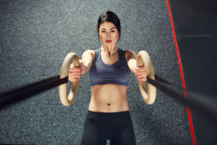 Crossfit workout on ring. Fitness woman holds training session crossfit on the rings in the gym. Muscular woman Caucasian appearance, brunette, is engaged in stock photos