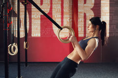 Crossfit workout on ring. Fitness woman holds training session crossfit on the rings in the gym. Muscular woman Caucasian appearance, brunette, is engaged in royalty free stock photo