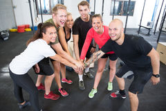 Crossfit workout team motivation. Happy and smiling crossfit workout group holding hands at the gym center Royalty Free Stock Photography