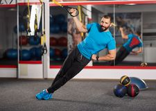Crossfit workout with trx straps. Fitness trainer working with trx straps for crossfit workout Stock Photo
