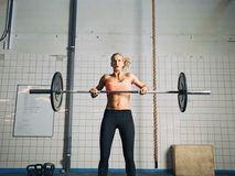 Crossfit young woman lifting heavy weights. Young strong woman practices cross fit in a gym. Fit female holding a barbell with weights for crossfit royalty free stock images