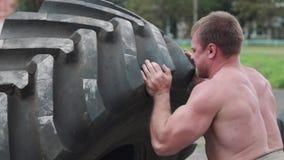Crossfiter de entrenamiento de los hombres, vueltas el neumático pesado almacen de video