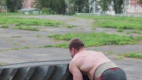 Crossfiter de entrenamiento de los hombres, vueltas el neumático pesado almacen de metraje de vídeo