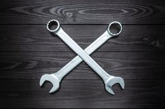 Crosshair of two chrome wrenches on dark wooden workbench stock photography