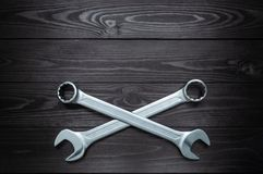 Crosshair of two chrome wrenches on dark wooden workbench royalty free stock photography