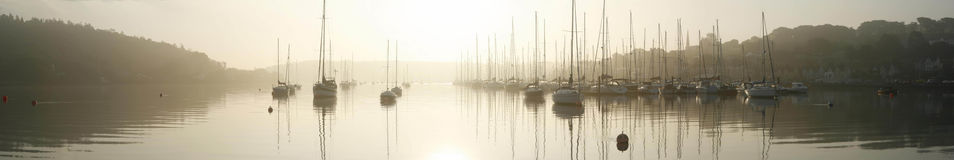 Crosshaven, Cork, Ireland. Yachts moored in river,  in misty sunrise with marina stock images