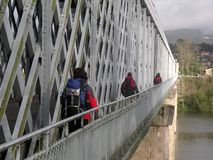 Crossing. Three backpackers walking, crossing a bridge Royalty Free Stock Photography