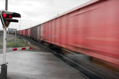 Crossing. Railway crossing with motion blurred ast freight train Royalty Free Stock Image