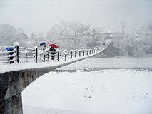 Crossing. Picturesque view of people crossing the entrance bridge at Shirakawa-go near Takayama in Japan on a snowy day stock photo