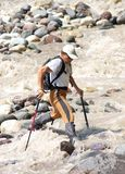 Crossing. A man crossing a mountain river. Sport and active life Stock Photos