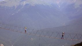 The crossing of the abyss in the mountains .People go on rope bridge across the chasm. Extreme tourism Stock Photo