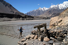Crossing The Bridge. Woman traveller crossing the unstable bridge across Hunza river in Karakorum royalty free stock photo