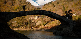 Crossing a bridge. Silhouette of a man crossing a bridge against mountain forest royalty free stock photos