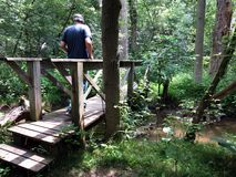 Crossing the Creek. Man crossing a footbridge over a creek in the woods royalty free stock photography