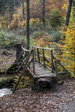 Crossing the creek. Old wooden bridge, crossing a creek in autumnal forest royalty free stock photography