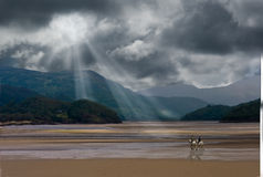 Crossing the Estuary. A storm brews as riders cross the Estuary at low tide near Barmouth Wales UK Stock Photo