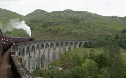 Crossing the Glenfinnan Viaduct on the Jacobite. Crossing the Glenfinnan Viaduct on board the Jacobite Steam train running from Fort William to Mallaig in the Stock Images