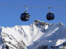 Crossing gondolas and mountain peak. Against blue sky in wintry alpine landscape, austria Stock Photo