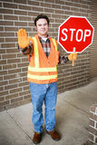 Crossing Guard at School. Handsome school crossing guard holding a stop sign Royalty Free Stock Image
