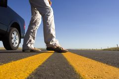Crossing the line. Man stepping onto the highway stock photography