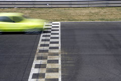 Crossing the line. Racing car in movement - conceptual (old car crossing the line and reaching the goal Royalty Free Stock Image
