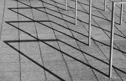 Crossing lines. Empty bicycle stands are throwing long shadows on a very late afternoon Royalty Free Stock Photography