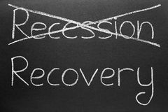 Crossing out recession and writing recovery. Crossing out recession and writing recovery on a blackboard stock photos