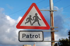 Crossing Patrol Sign. School crossing patrol sign attached to a rusty pole with a blue sky background Stock Photos