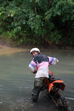 Crossing river. Man riding two wheel cross country vehicle Stock Images